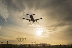 Airplane landing at dusk. Royalty Free Stock Photo