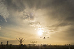 Airplane landing at dusk. Royalty Free Stock Images