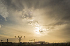 Airplane landing at dusk. Royalty Free Stock Photos