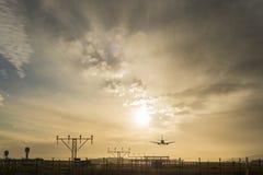Airplane landing at dusk. Royalty Free Stock Image