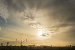 Airplane landing at dusk. Royalty Free Stock Photo