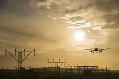 Airplane landing at dusk. Royalty Free Stock Image