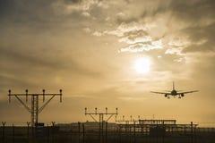 Airplane landing at dusk. Stock Photo