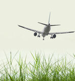 Airplane landing in front of grass Stock Image