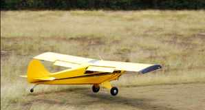 Airplane landing in grass. Yellow Airplane near to land in grass airfield Stock Image