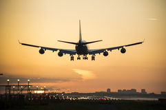 Airplane landing with an orange sky at the background. Royalty Free Stock Photos