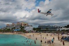 Airplane landing over beach in Saint Maarten. Airplane landing over a crowded beach on the island of Saint Maarten in the Caribbean royalty free stock photo