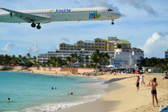 Airplane Landing over Busy Beach Stock Photo
