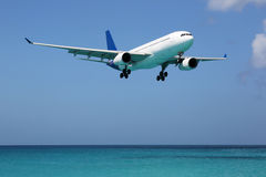 Airplane landing over the sea on vacation Royalty Free Stock Photo