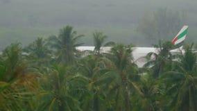 Airplane landing at Phuket airport at rain stock video
