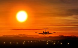 Airplane landing - private jet silhouette on sunset. Airplane silhouette landing at the airport during sunset. Sun, shape of private jet plane and flashing stock photography