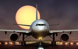 Airplane landing on runway during sunset Stock Image