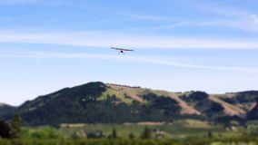 Airplane Landing Sequence Tilt Shift. V32. Two clips of small airplanes landing at little airfield with scenic backgrounds. Tilt shift effect used stock footage
