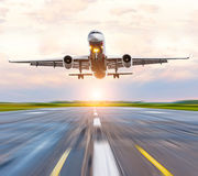 Airplane landing speed on the runway at the airport at sunset dawn Royalty Free Stock Photo