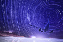 Airplane landing with startrails as background Stock Photo