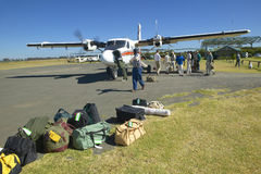 Airplane on landing strip headed to Masai Mara Kenya with luggage to be loaded Royalty Free Stock Images