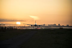 Airplane is landing during sunrise. Royalty Free Stock Photography