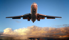 Airplane landing at sunset Stock Images