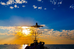 Airplane  landing at sunset Stock Photography
