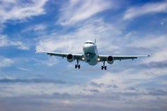 Airplane landing at sunset Stock Image