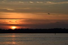Airplane landing at sunset over river Stock Photography