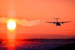 Airplane landing in sunset Stock Images