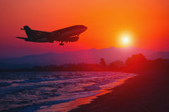 Airplane landing at sunset. Stock Photos