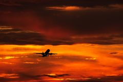 Airplane landing or takeoff in the sunset with red sky in Bucharest international airport , Plain spotting royalty free stock photo