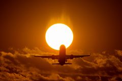 Airplane landing or takeoff in the sunset with red sky in Bucharest international airport , Plain spotting. And aviation photography with sun crossing stock images