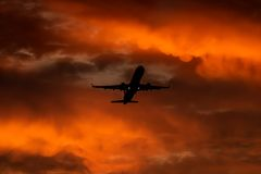 Airplane landing or takeoff in the sunset with red sky in Bucharest international airport , Plain spotting stock photo