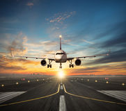 Airplane landing to airport runway in sunset light. Passengers airplane landing to airport runway in beautiful sunset light, silhouette of modern city on Stock Photo