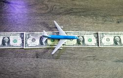 The airplane lies on a strip of one dollars. Landing strip for airplanes of dollars