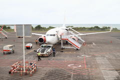 Airplane Lion Air on airport. Airplane of Indonesian airlines Lion Air getting ready on airport in Denpasar Bali, Indonesia with sea behind Stock Image