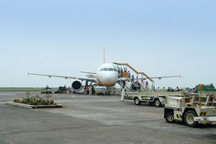 Airplane loading passengers and luggage. Commercial airliner loading luggage and cargo while passengers enter it, on the tarmac of the rural small airport (DPL royalty free stock images