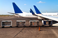 Airplane with luggage cars Stock Images
