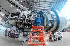 Airplane mechanic diagnose repairs jet engine through open hatch. Airplane mechanic diagnose repairs jet engine through open hatch royalty free stock photography