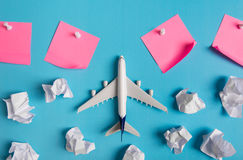 Airplane model flying among paper clouds and pink paper noted. Airplane model flying among paper clouds and pink paper noted, Traveling concept Stock Photo