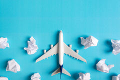 Airplane model flying among paper clouds. Airplane model flying among paper clouds, Traveling concept Stock Photo