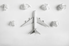 Airplane model flying among paper clouds. Airplane model flying among paper clouds, Traveling concept, on white background Royalty Free Stock Images