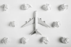 Airplane model flying among paper clouds. Airplane model flying among paper clouds, Traveling concept, on white background Royalty Free Stock Image