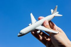 Airplane model in hand on sunny sky. Concepts of travel, transportation, transport, dreaming about holidays. Royalty Free Stock Images
