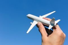 Airplane model in hand on sunny sky. Concepts of travel, transportation, transport, dreaming about holidays. royalty free stock image