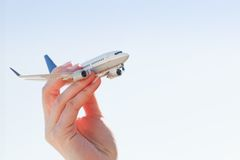Airplane model in hand on sunny sky. Travel, transportation Royalty Free Stock Photo