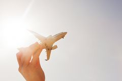 Airplane model in hand on sunny sky. Travel, transportation Royalty Free Stock Images