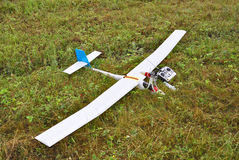 Airplane model landed. Red and white radio controlled airplane with methanol engine on a grassy field stock images