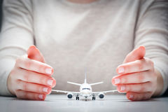 Airplane model surrounded by hands in gesture of protection. Aircraft industry safety, insurance Royalty Free Stock Photos