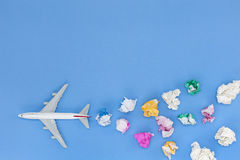 Airplane model with various paper ball on blue background with c Stock Photos