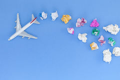 Airplane model with  various paper ball on blue background with Royalty Free Stock Photos