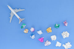 Airplane model with  various paper ball on blue background with Stock Photos