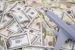 Airplane on Money, the rising costs of airline travel. Airline business Royalty Free Stock Photography